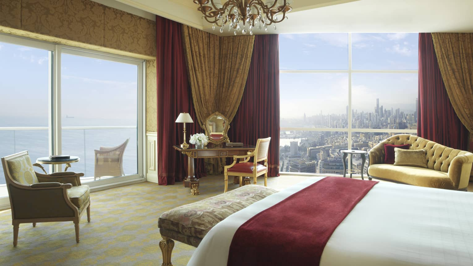 White bed with red suede sash, antique-style bench, green-and-gold leaf armchair, corner suite views of water and city