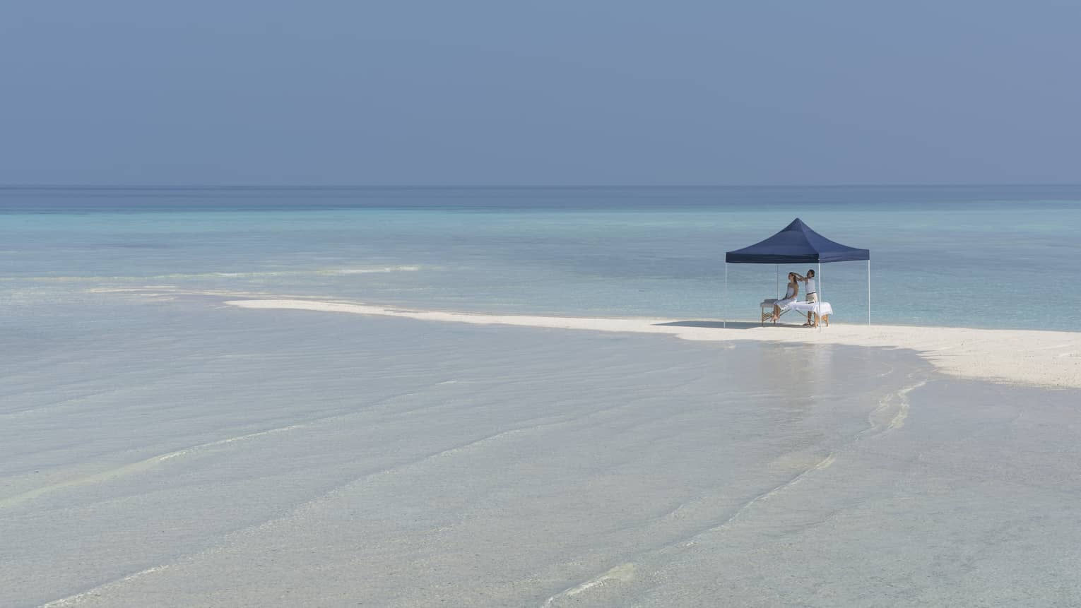A four seasons guest receives a massage under a blue tent on the beach in Maldives