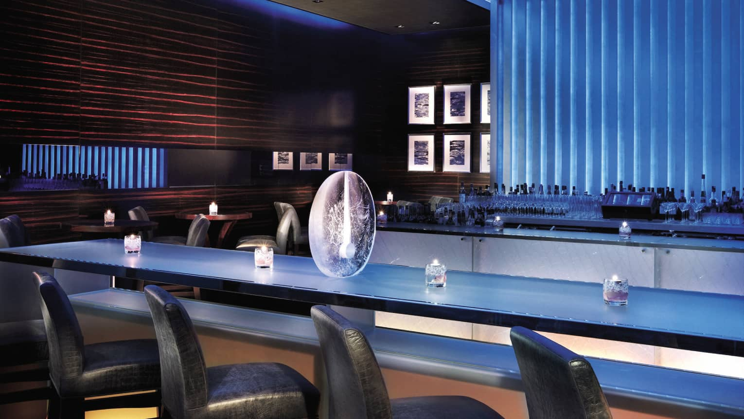 Bar Azul leather chairs along blue bar, glass candles and large round vase, wood panel wall