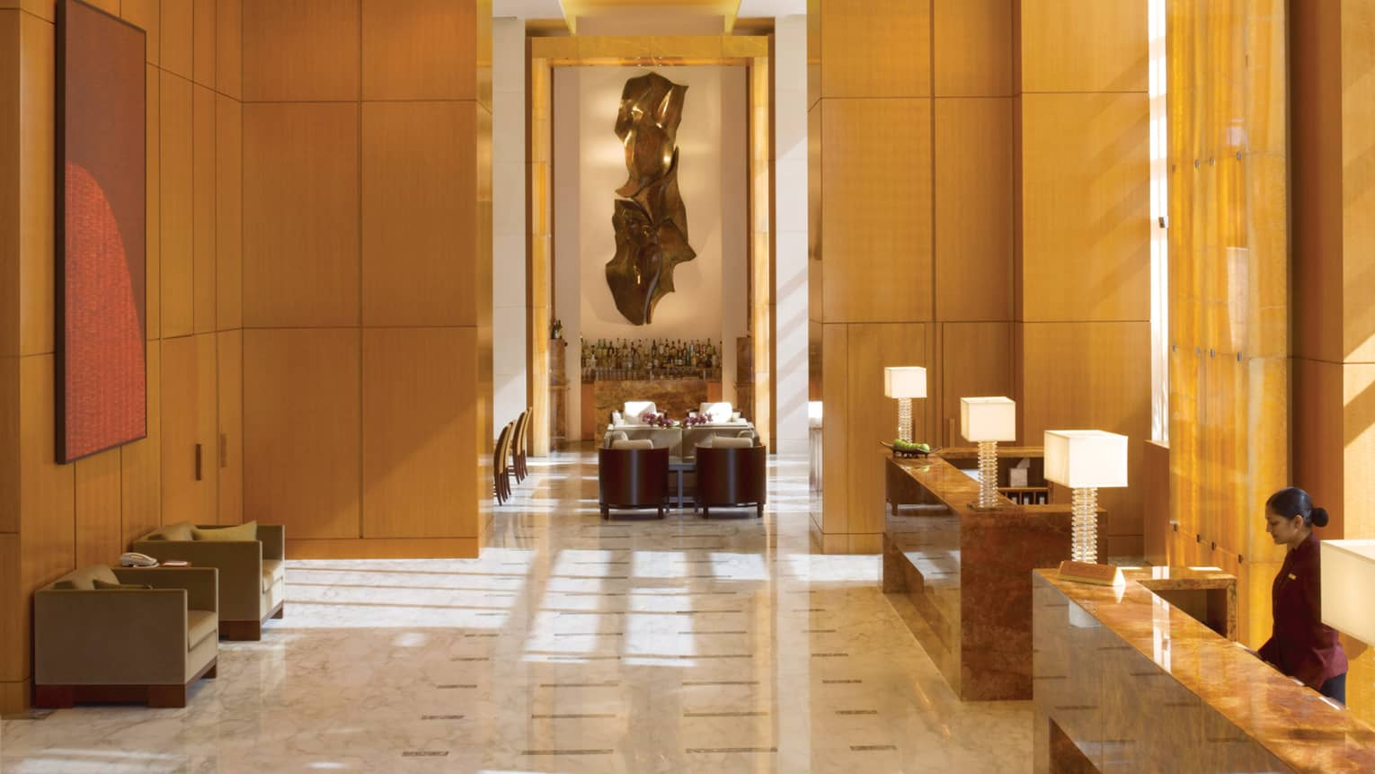 Hotel lobby with soaring ceilings over wood panel walls, marble floors, reception desks