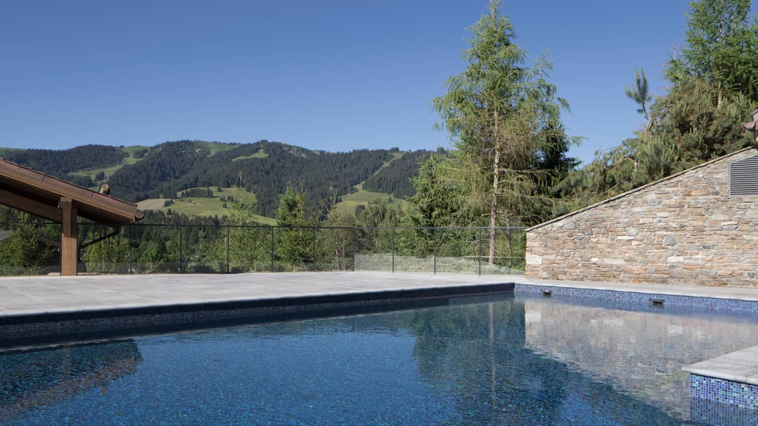 Heated outdoor pool under stone wall, green mountains