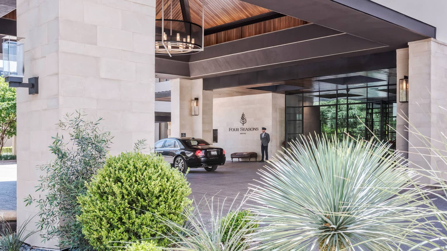 Hotel staff stands near door, black car under Four Seasons Hotel Austin entrance