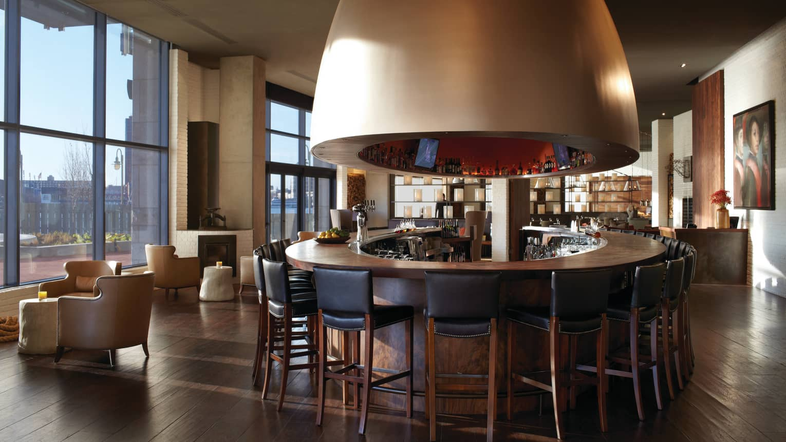 Round bar with black stools under large dome in sunny dining lounge