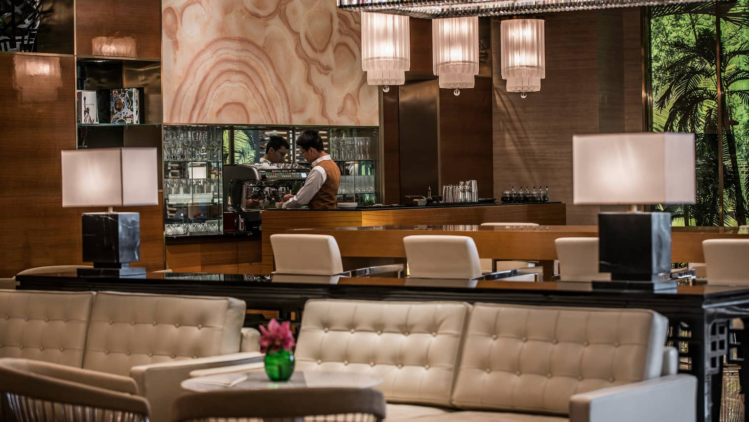 La Sala staff makes coffee at espresso machine behind wood bar, white leather banquettes