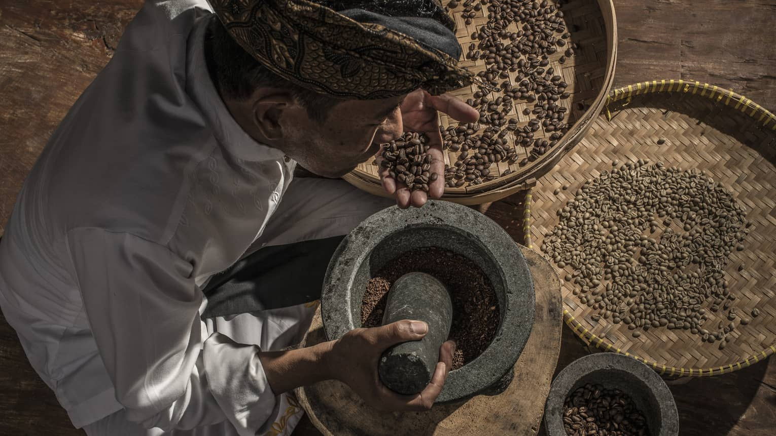 A coffee grower with coffee beans in a large mortar and pestle at Four Seasons Bali and Jimbaran Bay