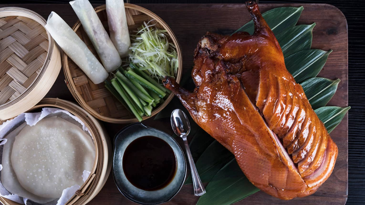 Aerial view of Peking Duck sliced on side, bamboo basket with spring rolls, onions