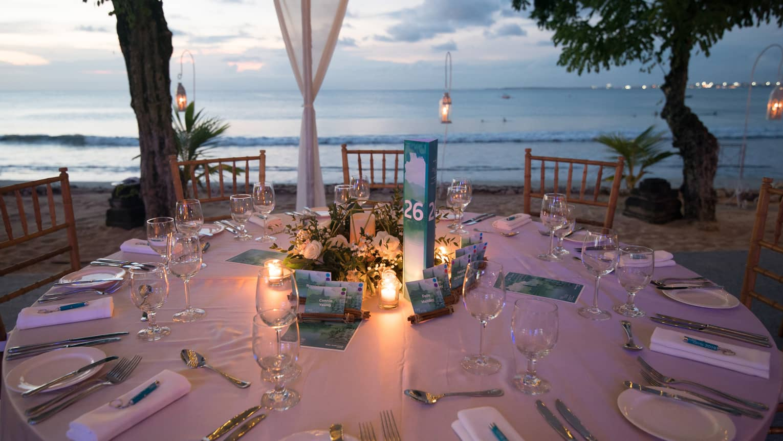 Round banquet dining table with candles overlooking ocean at dusk