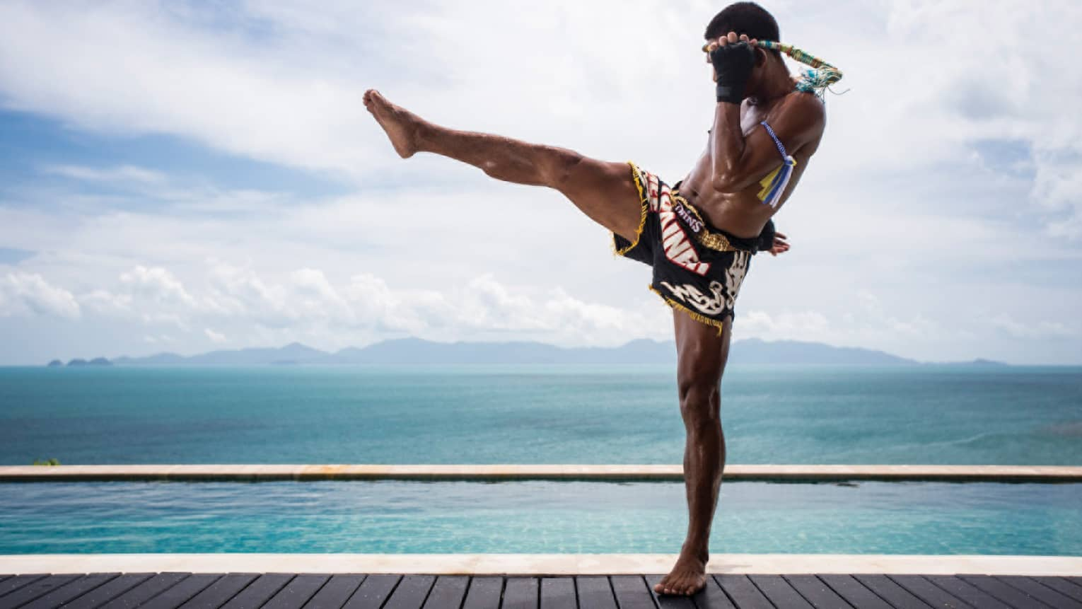 Side view of Muay Thai kick-boxer wearing shorts, doing leg kick on swimming pool deck in front of ocean