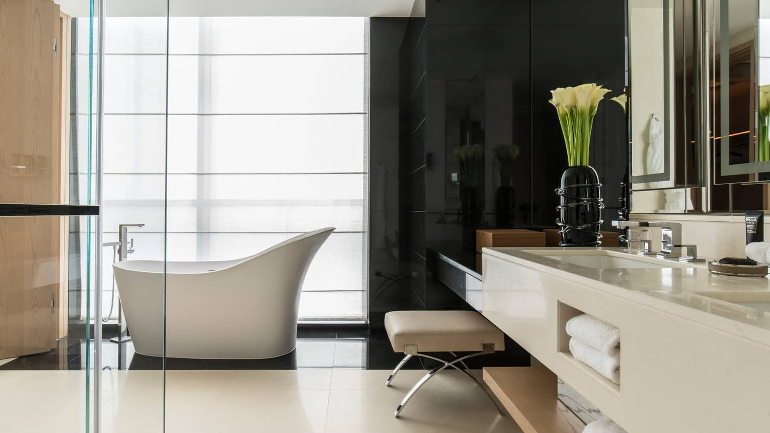 Large Four Seasons Deluxe Executive Suite bathroom with modern freestanding white tub, sink with fresh white flowers