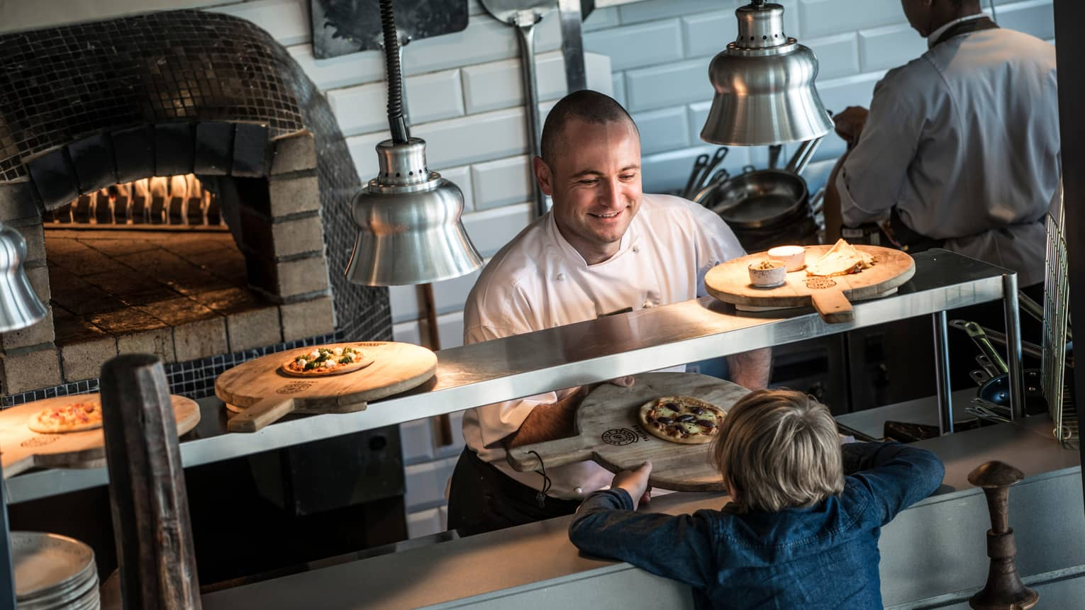 Chef at open kitchen line near wood-burning oven passes wood tray with small pizza to child