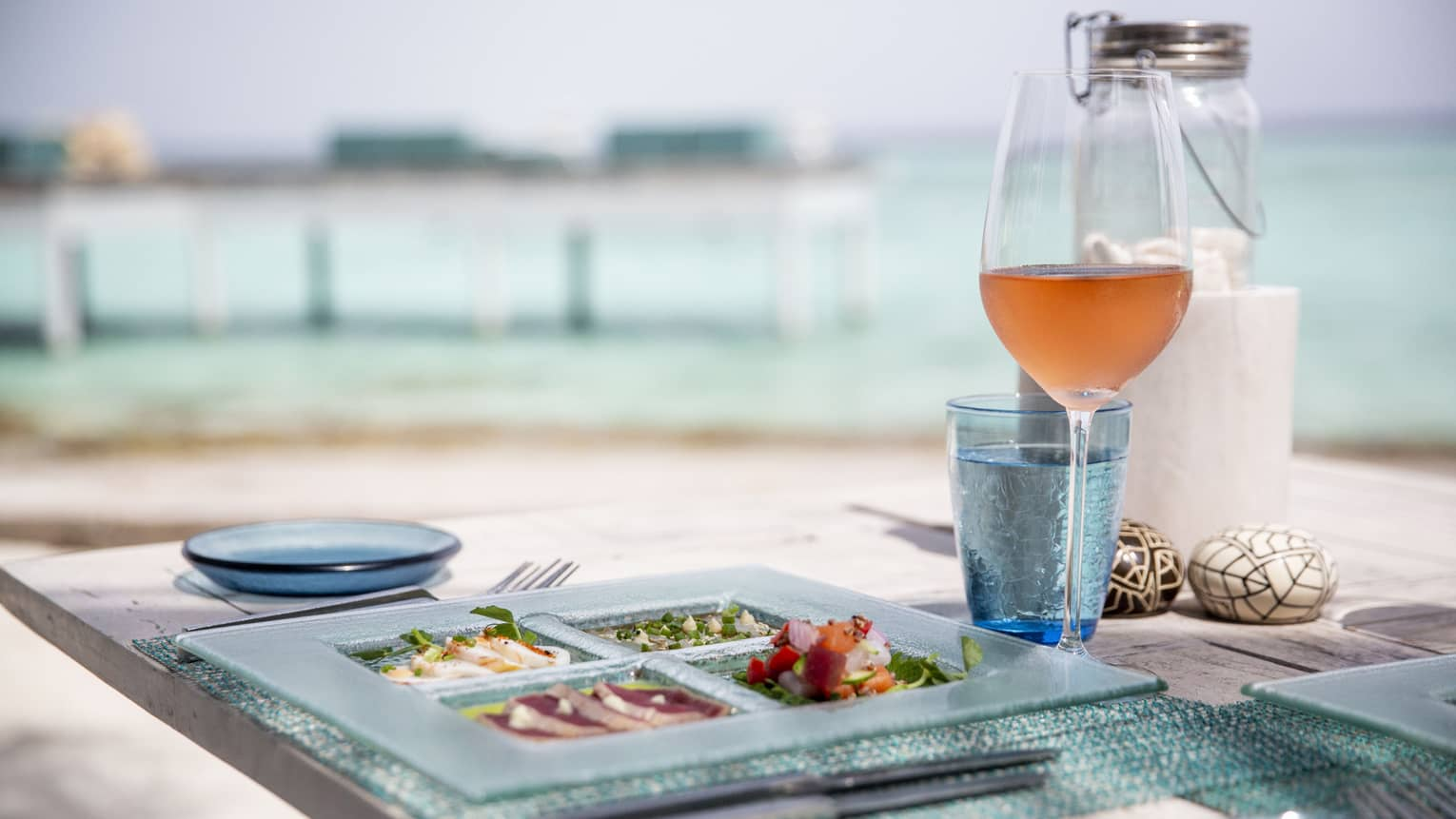 Outdoor dining table with glass plate with sashimi, wine overlooking lagoon