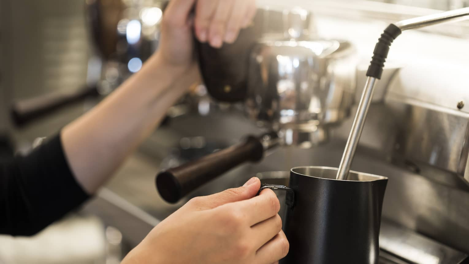 Close-up of hands with milk steamer at espresso machine