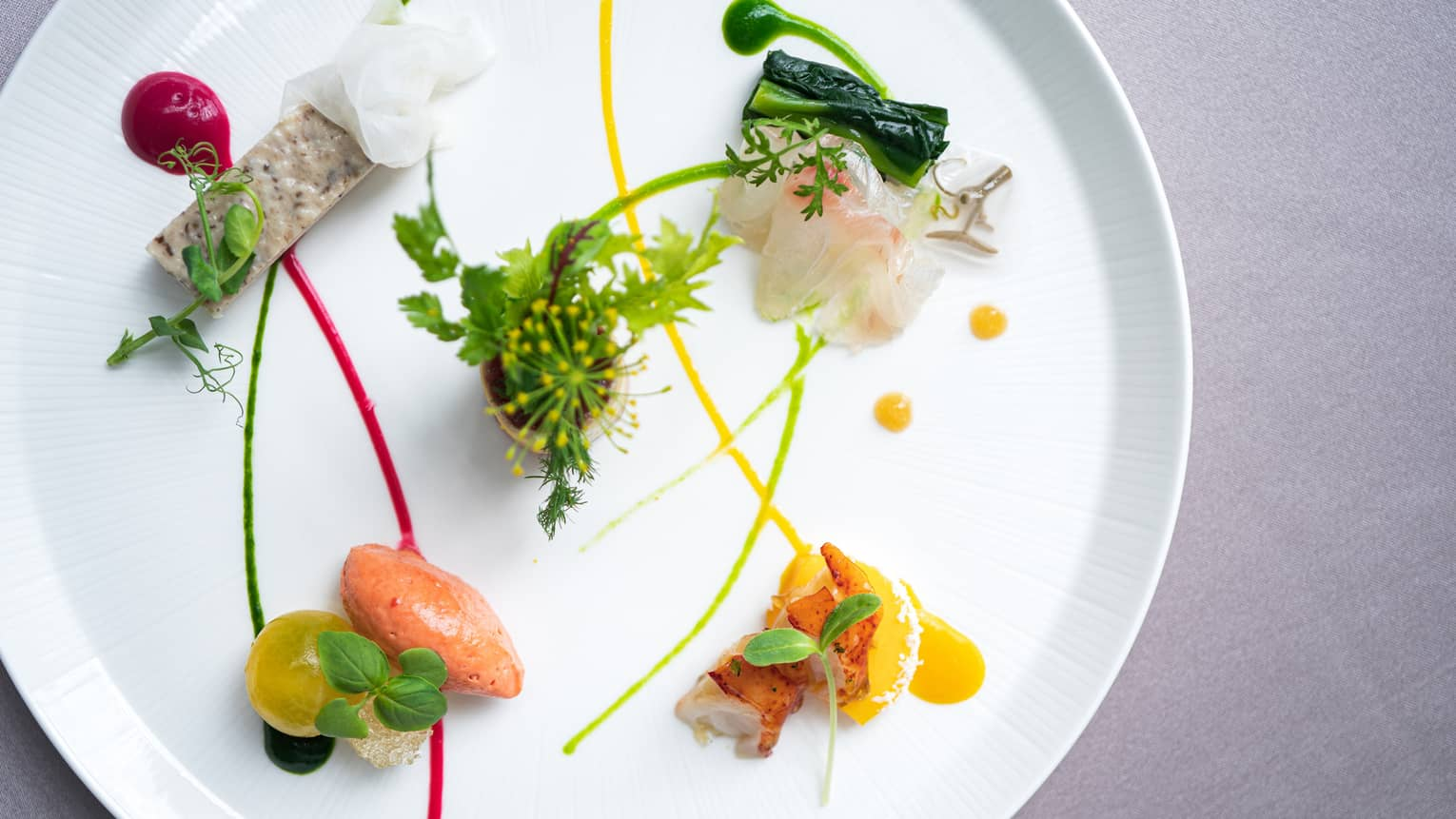Small appetizers arranged on plate with artistic garnish