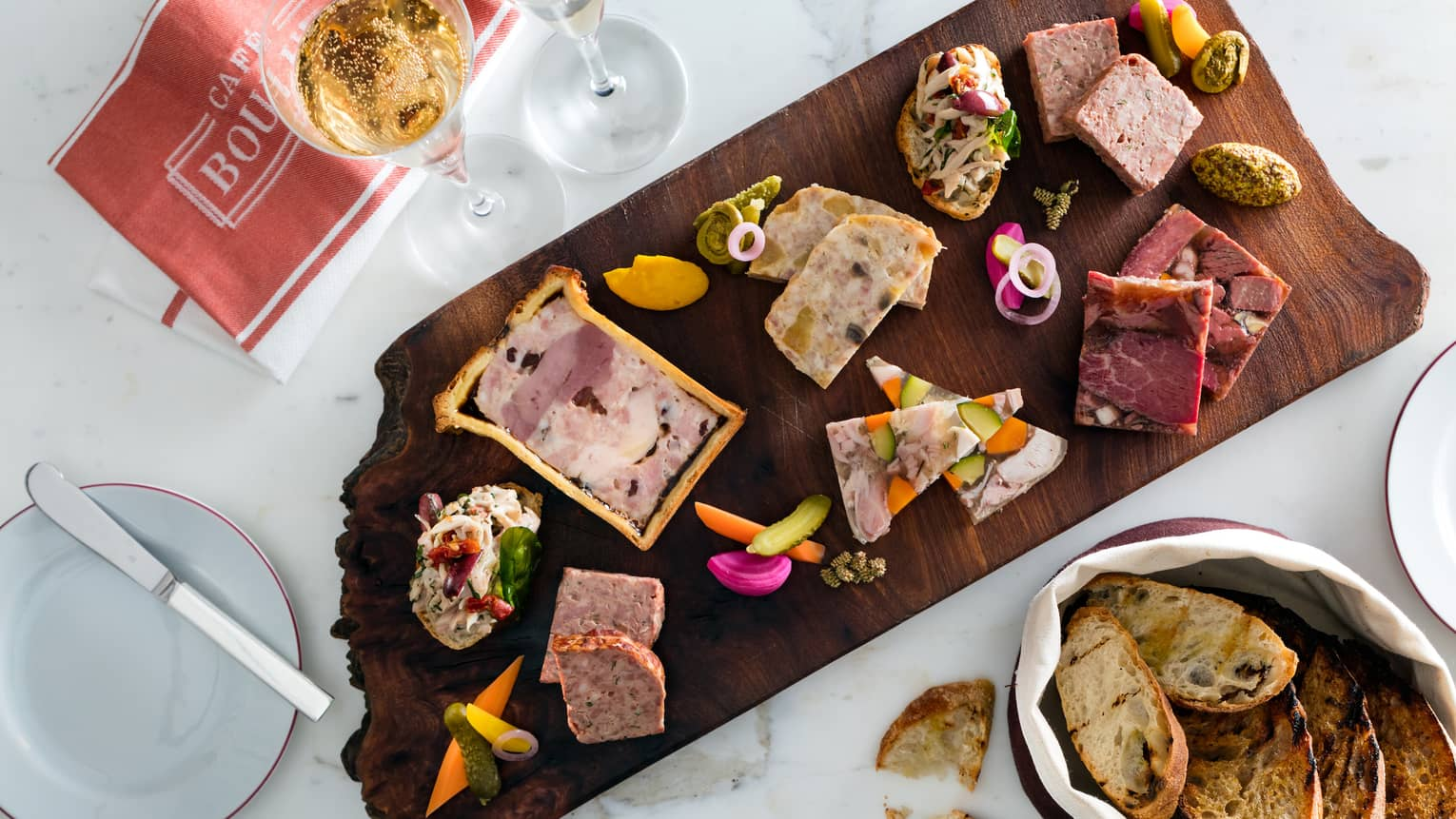 Aerial view of charcuterie board with pate, pickles, toasts