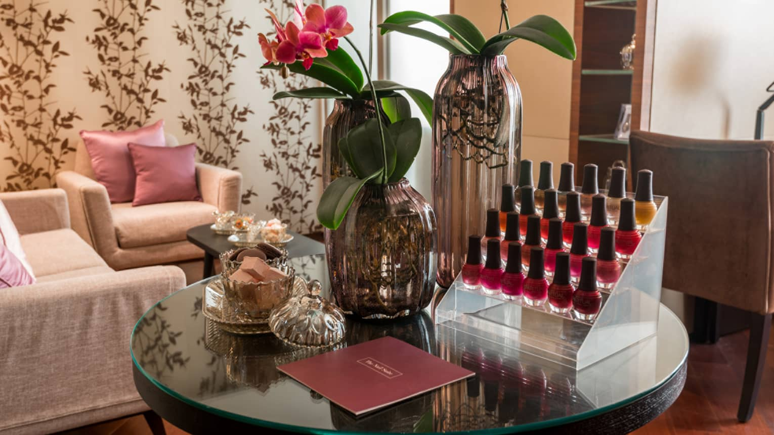 Close-up of The Nail Suite round table with trays of nail polish, flowers in vase