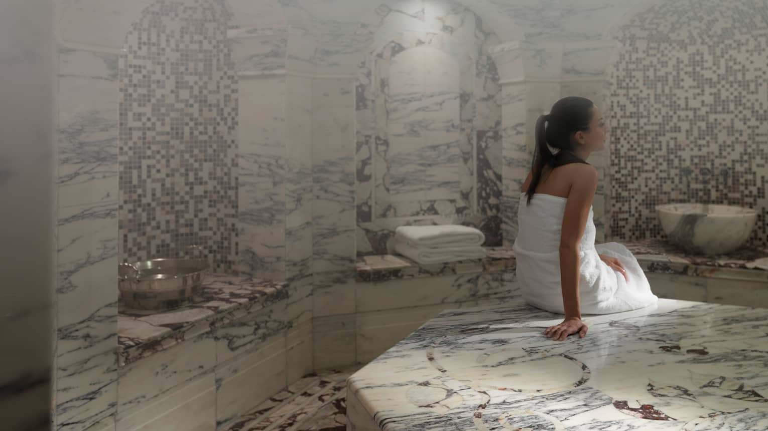 Back of woman in white towel on black-and-white marble ledge in Hammam steam room