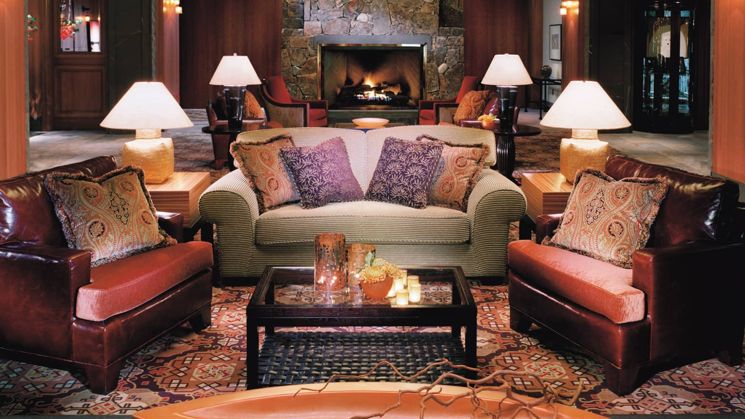 Lobby living area with plush sofa and armchairs, patterned pillows in front of large rustic  stone fireplace