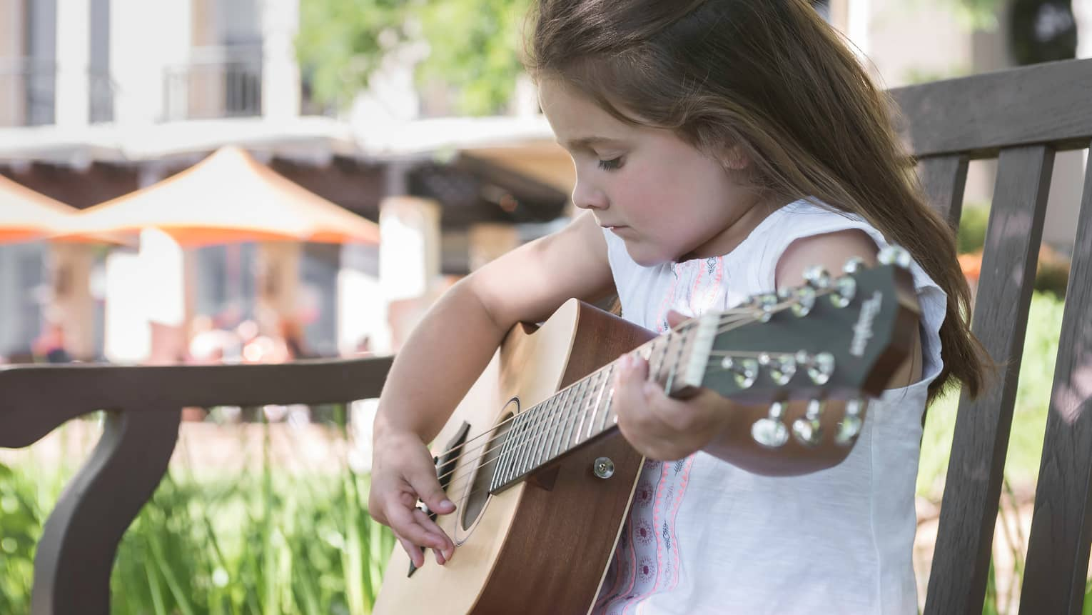 Young girl plays guitar on patio chair