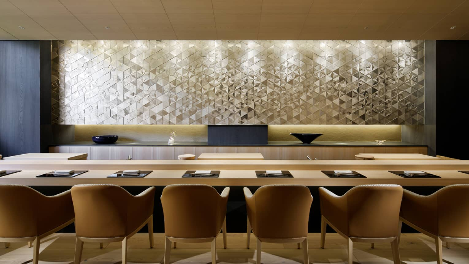 Sushi Wakon large chairs line light wood bar under silver tile wall