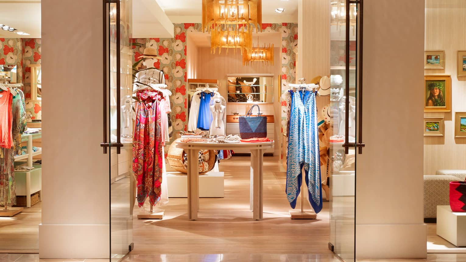 View through doors into boutique lobby store with colourful dresses on racks, table with scarves, purse
