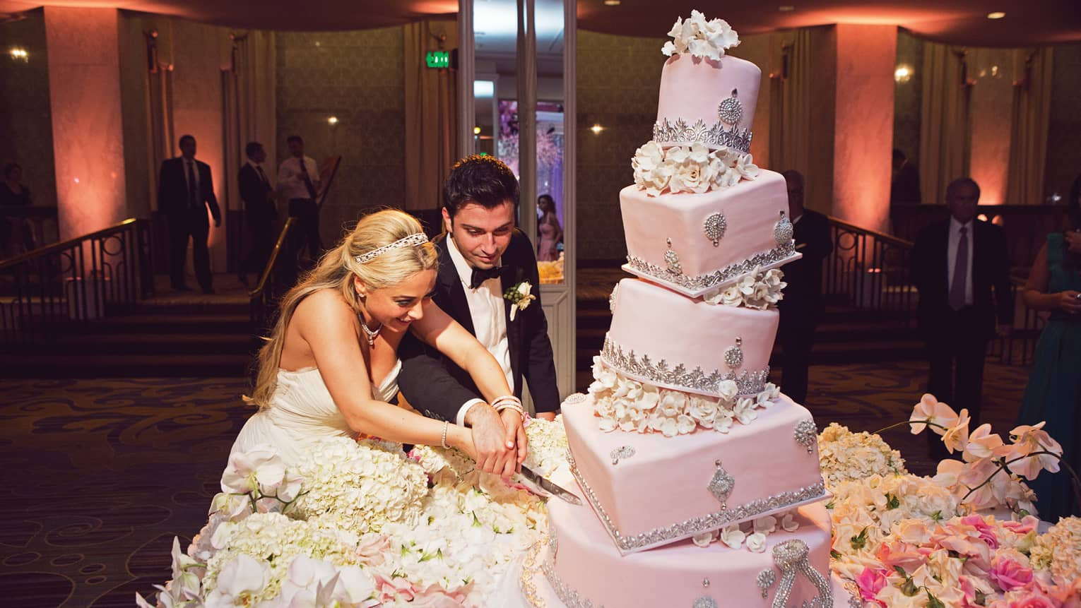 Bride and groom cut large, five tiered pink layer cake at wedding reception
