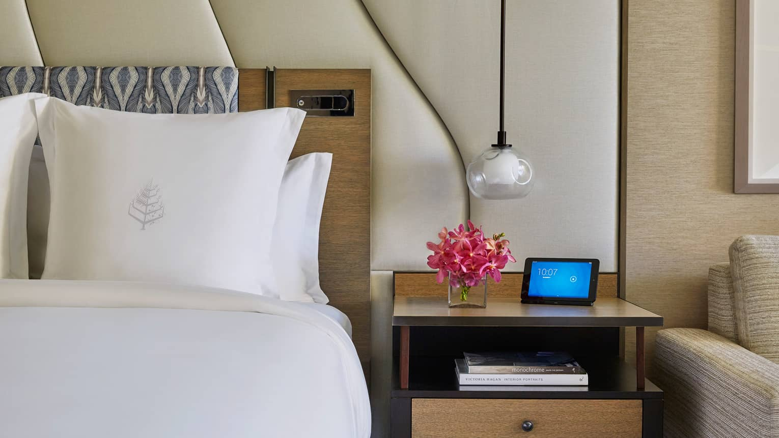 Hotel room with white bed, Four Seasons logo on pillow, large white padded headboard, flowers and ipad on nightstand