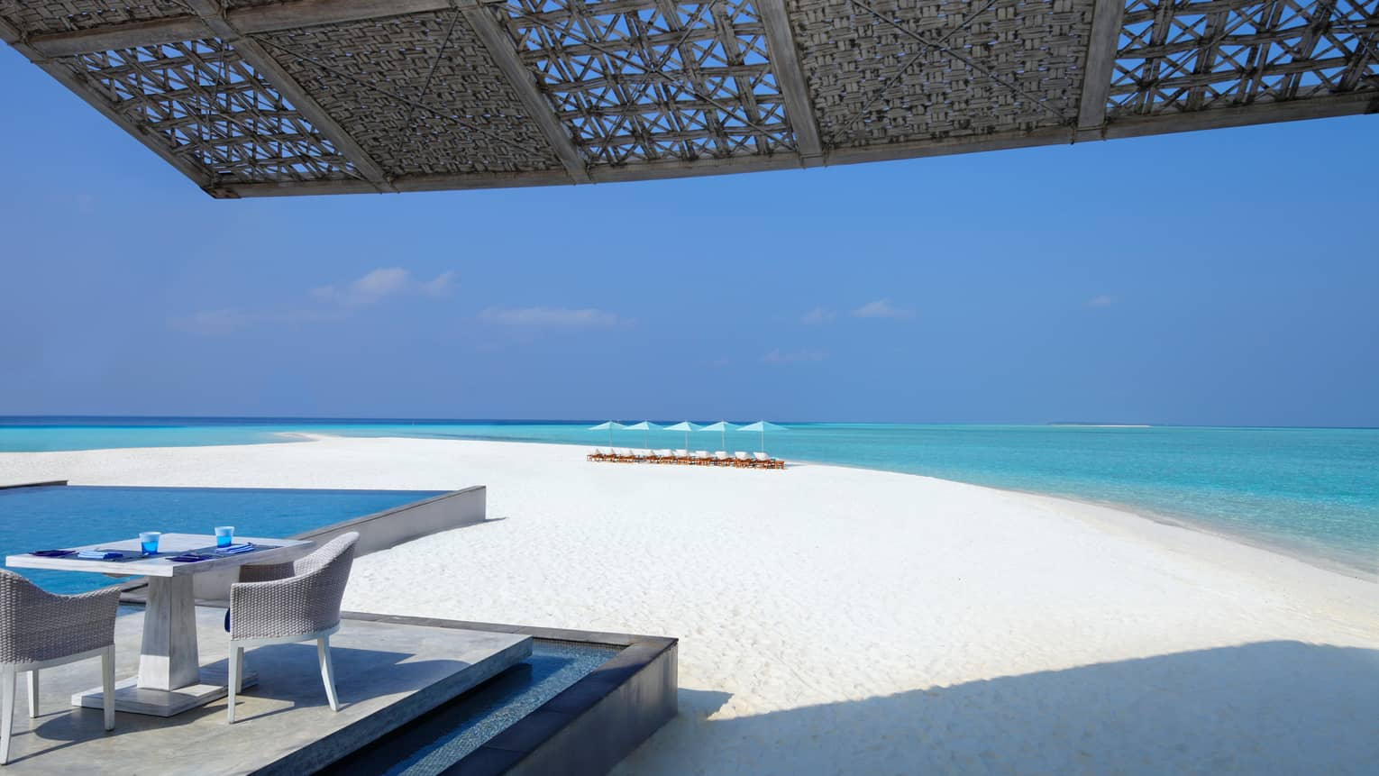 Woven roof, small white wicker patio, table on patio platform by long white sand beach, ocean