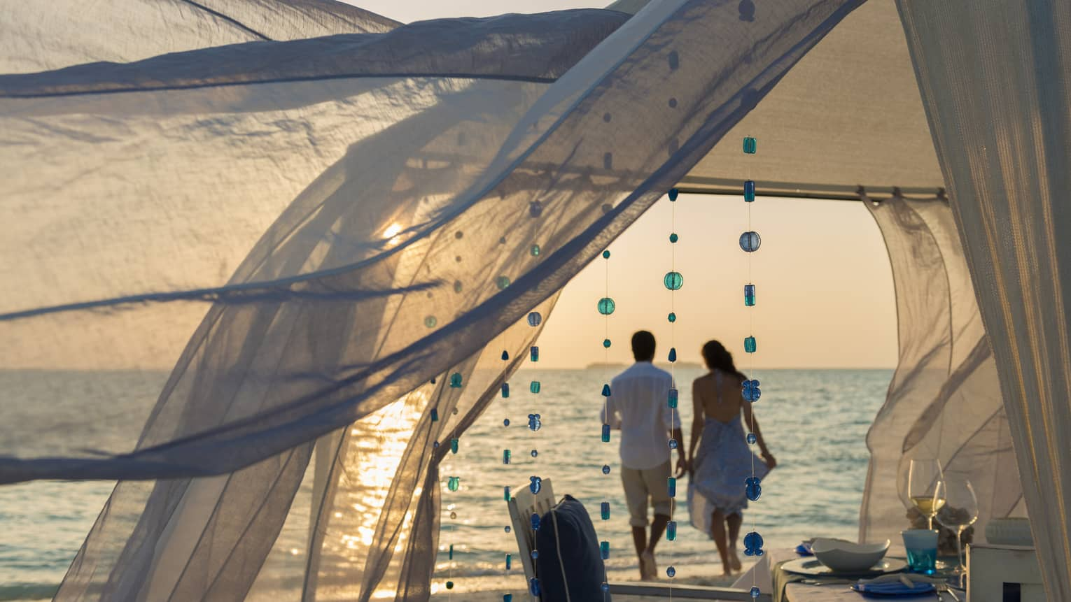 Sheer curtains blow in breeze, small blue beads hang from string, woman and man hold hands on beach in background