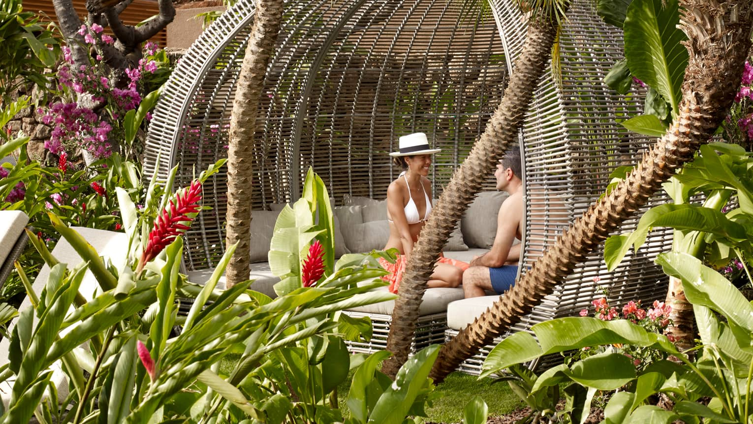 Couple sits in large wicker cabana in Pool Sanctuary outdoor patio lounge, tropical gardens