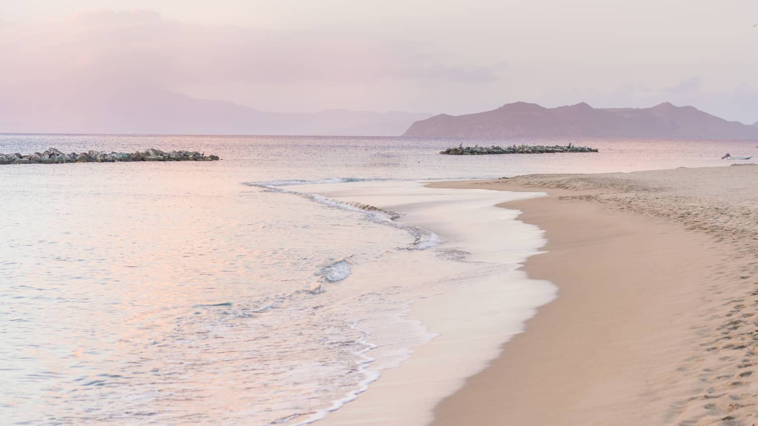 Calm tides on edge of white sand beach, pink sunset reflected on water