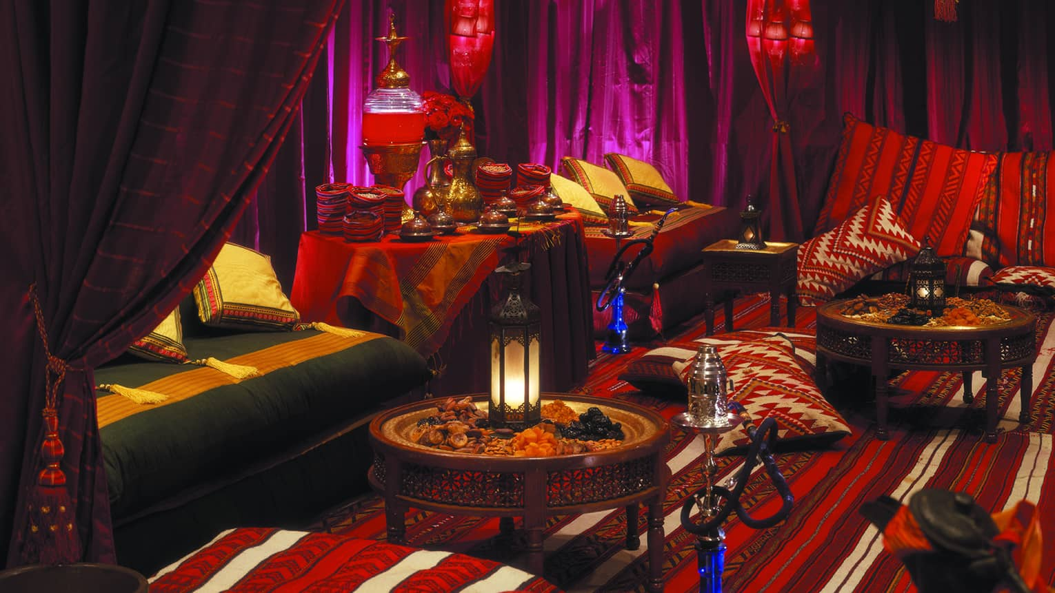 Arabian banquet seating area with pillows, curtains in deep reds and purples, lanterns