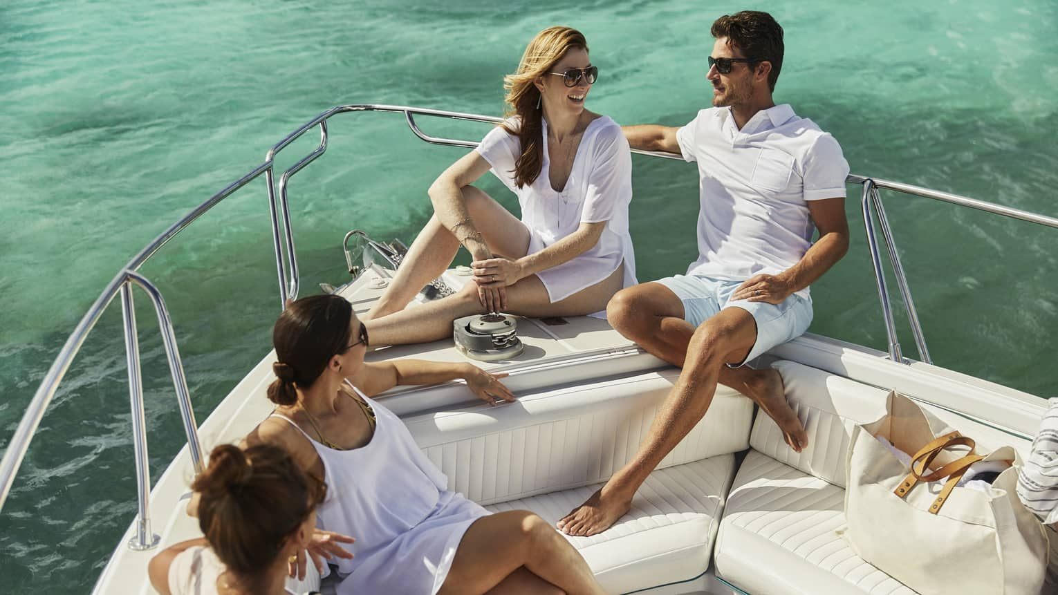 Man and woman wearing sunglasses sit on end of boat, talking to two women on bench