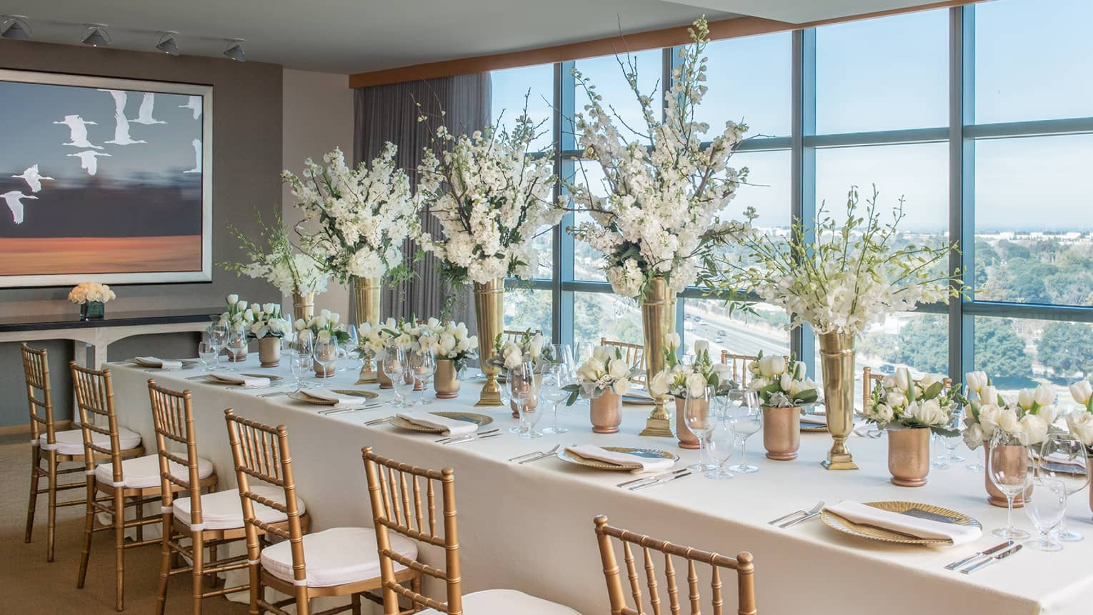 Sky Suite long dining table with white linens, flower centrepieces by window overlooking Palo Alto