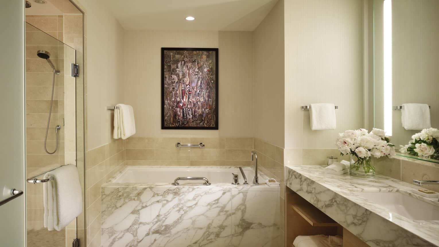 Large white marble bathroom with deep tub in between glass shower, sink and vanity