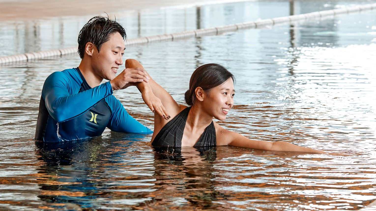 Swimming instructor helps woman position arm in indoor swimming pool