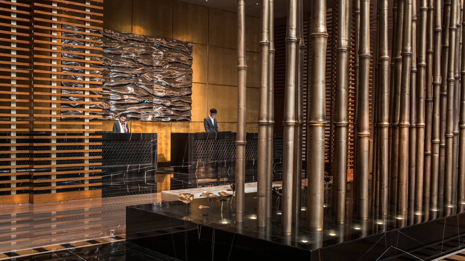 Two hotel staff behind reception desks under large wave-like wall sculpture, wood panel wall