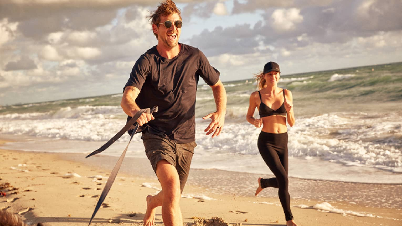 Man and woman jog along the beach with their dog