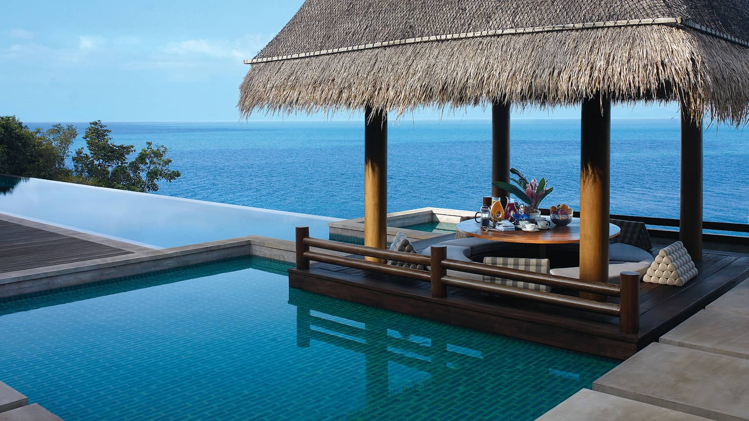 Infinity pool overlooking the Gulf of Thailand with a thatched-roof cabana
