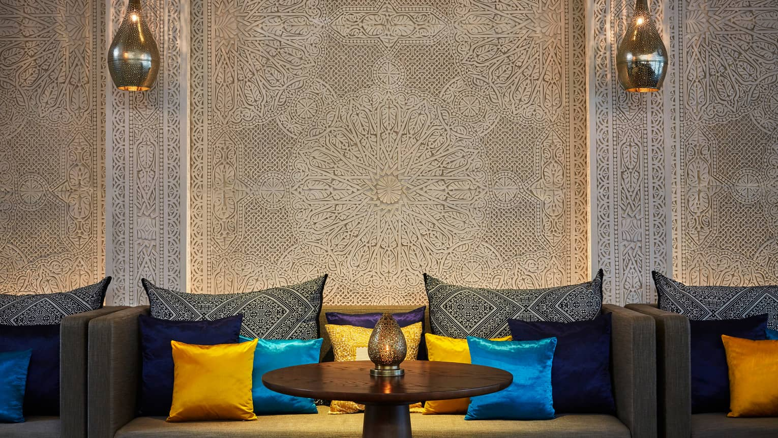 Decorative white wall, sofa with blue and yellow silk pillows, Moroccan lanterns