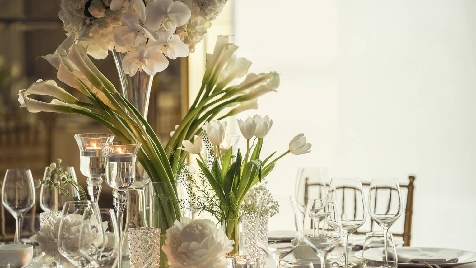 Western Banquet room dining table with glassware, long stemmed white flowers in vase