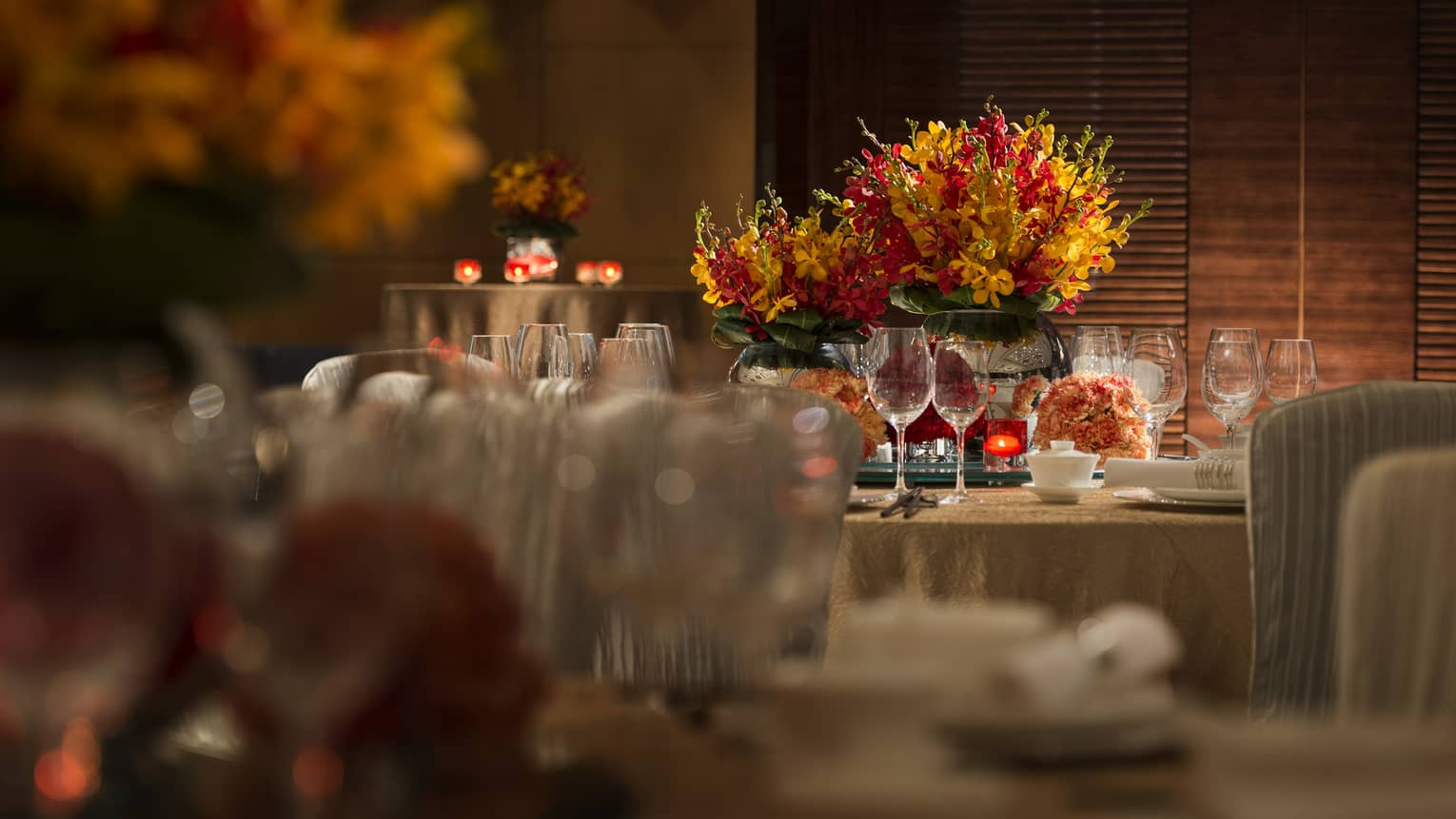 Orange and red flowers, candles on round banquet tables with gold linens