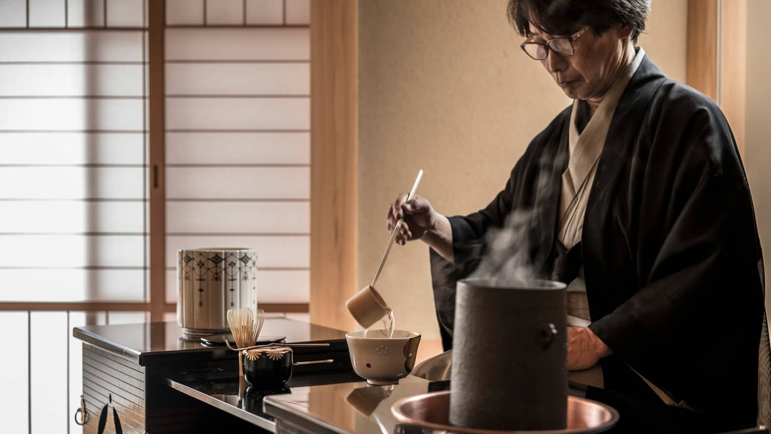 Man ladles hot tea into cup on table in teahouse by steaming pot