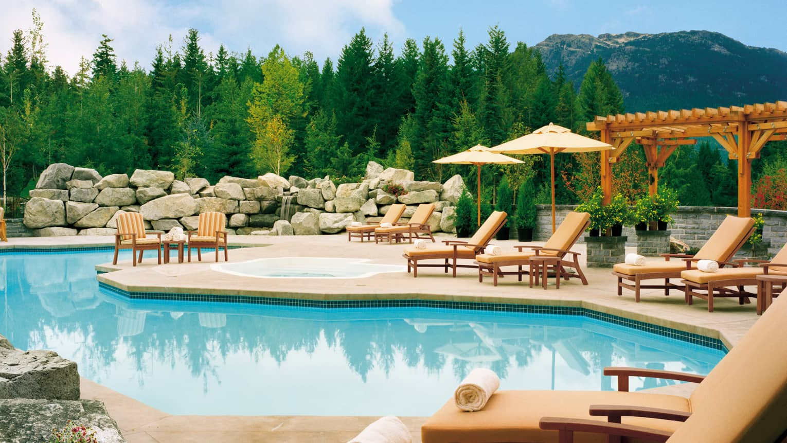Outdoor swimming pool, patio chairs and umbrellas during summer with green trees, mountain in distance