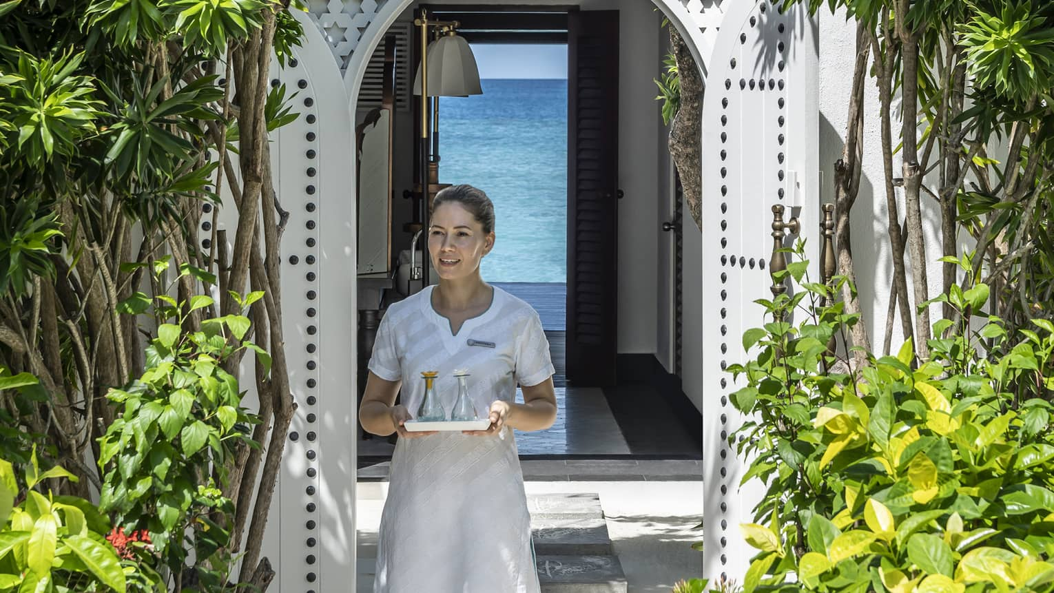 A four seasons spa member carries a tray of food through a shrubbery lined archway