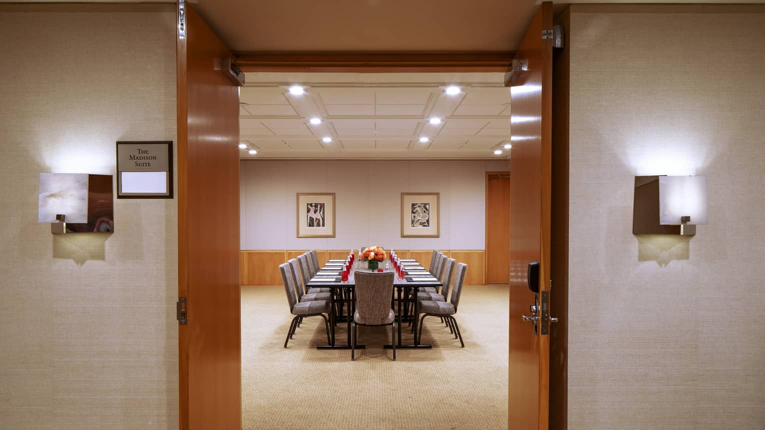 Two dark wooden doors are opened to reveal a function room with a long rectangular boardroom table with an orange floral arrangement in the center