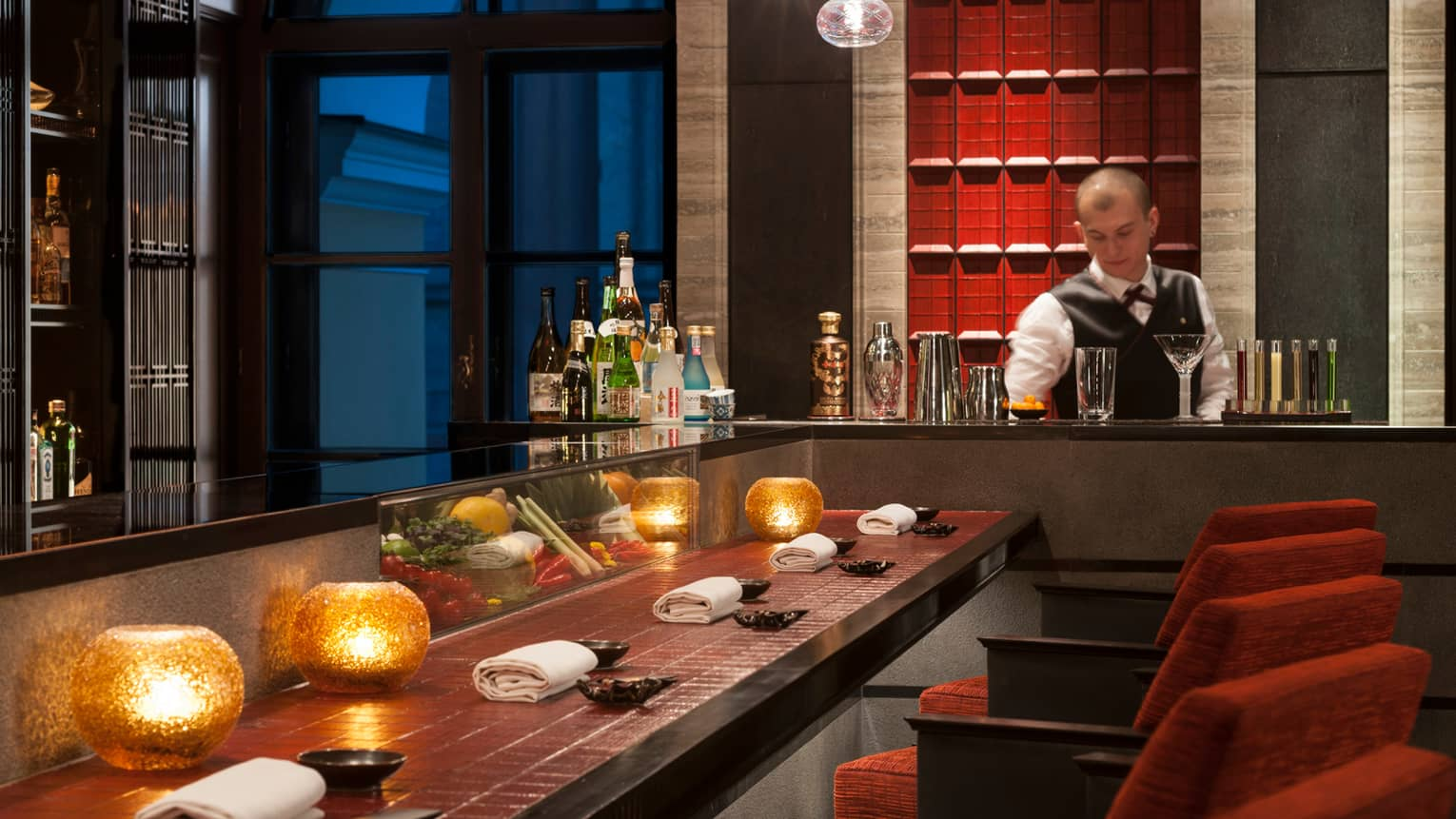 Bartender mixes drinks in front of long red tile bar with glowing orange candle votives, red stools