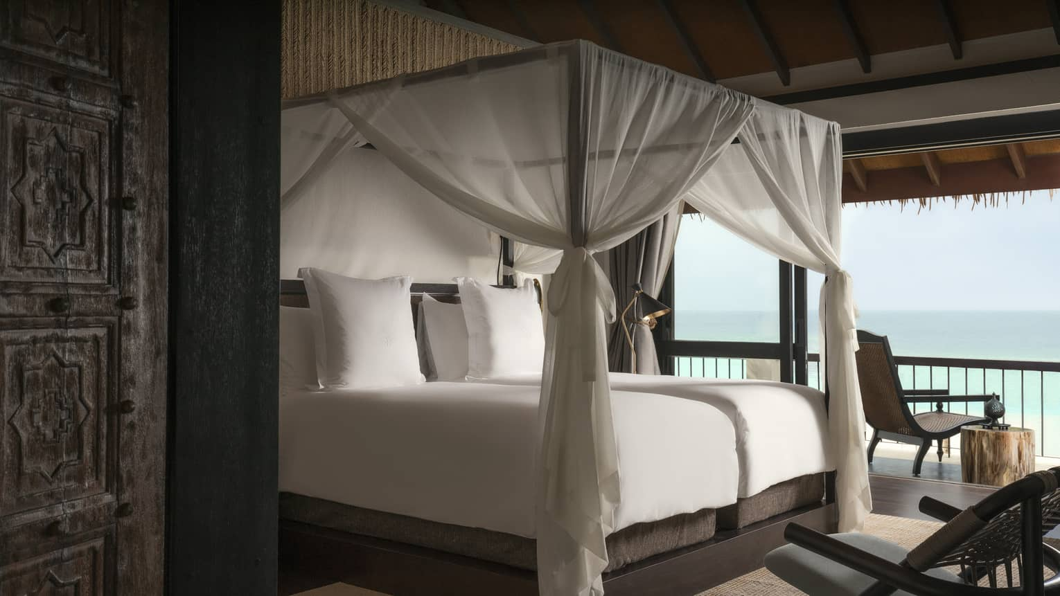 Villa poster bed with white canopy by open wall with ocean views