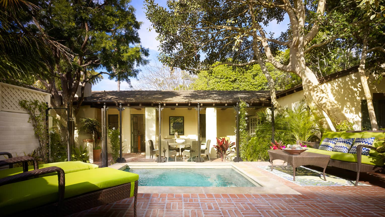 Bungalow backyard with plunge swimming pool, patio, wicker lounge chairs with green cushions