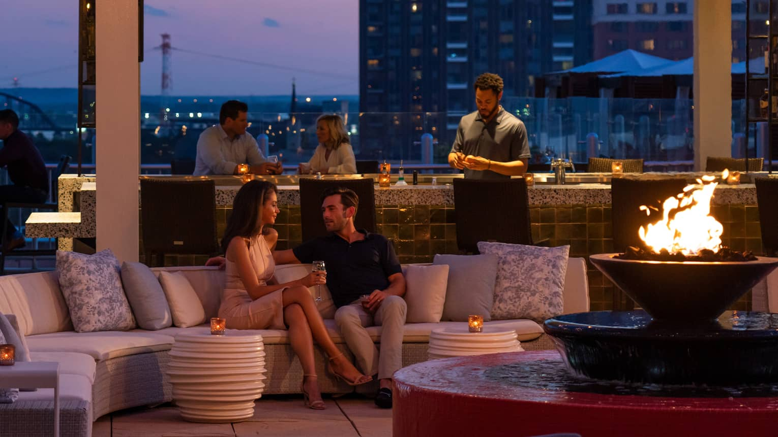 The sky is dark beyond the cinderhouse rooftop bar – furnished with a curved sectional, fire pit, hanging lights and people socialize