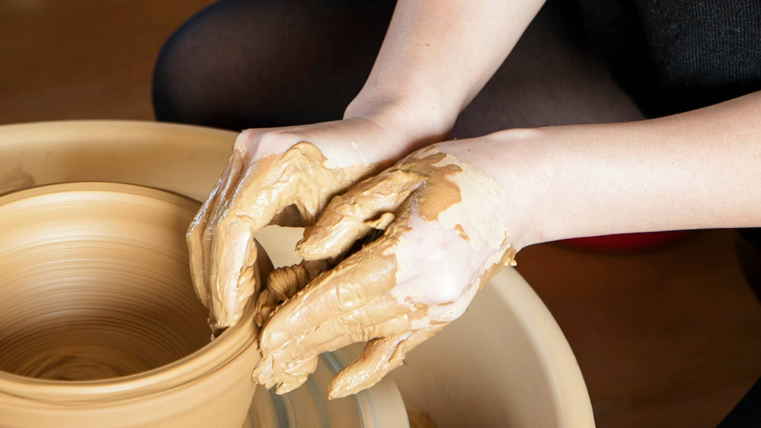 Close-up of hands covered in clay making pottery